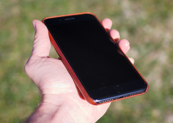 Hand holding iphone in brown leather case